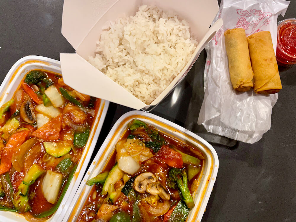 Two vegetable dishes with rice and fried spring rolls