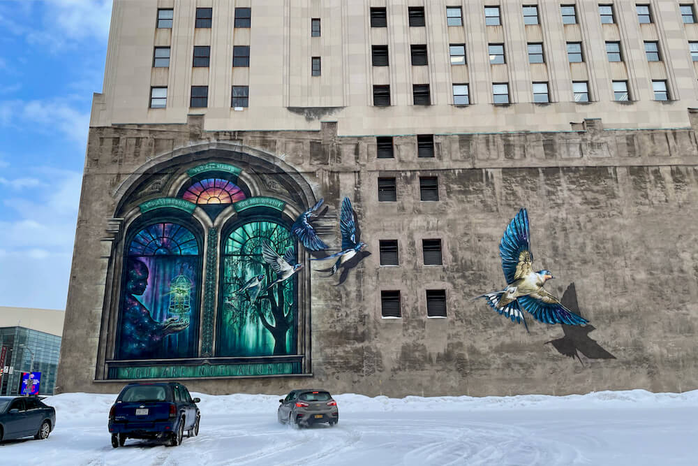 Colorful mural of person holding an empty bird cage and birds taking flight